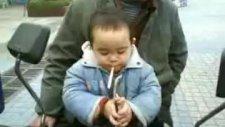 2 Yasindaki Cocuk Elinde Sigara Ve İciyor Japon